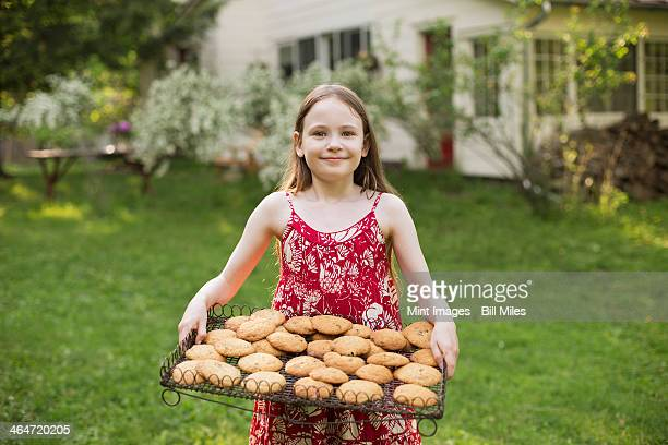 Baking homemade cookies. A young girl holding a tray of fresh baked cookies.