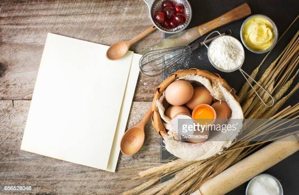Baking ingredients and utensils on rustic wooden background.