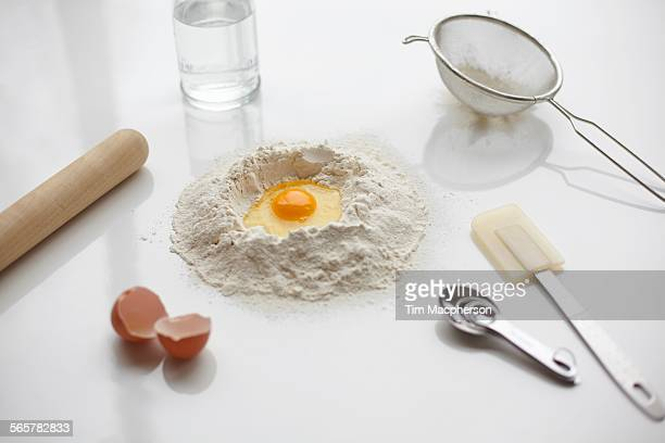 Baking preparation with raw egg in center of flour stack and kitchen utensils