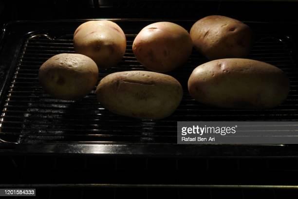 baking raw potatoes in home oven - rafael ben ari stock-fotos und bilder