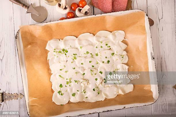 Baking tray of slices of mozzarella, oregano, cream cheese and egg