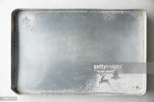 A baking tray with Christmas shapes dusted in icing sugar