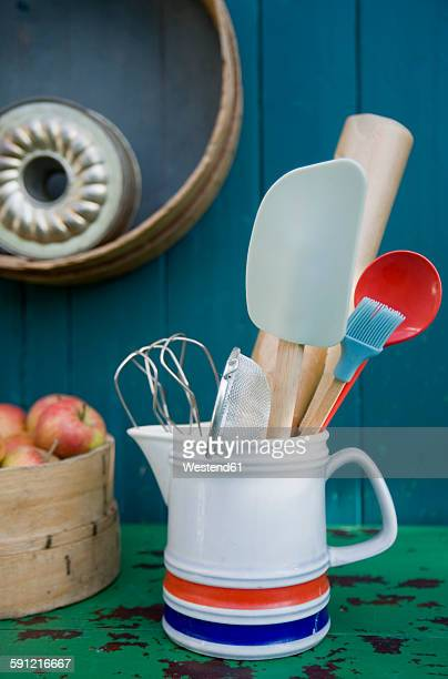 baking utensils in pitcher, cake pans on wall - basting brush stock photos and pictures