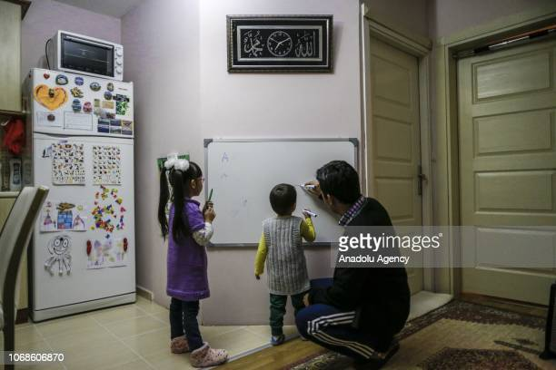 Bakit Kalmuratov a journalist draws on a lesson board for his children five years old Naile and 3 years old Omer Adil at his home in Ankara Turkey on...