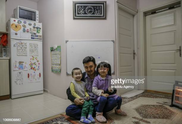 Bakit Kalmuratov a journalist poses for a photo with his children five years old Naile and 3 years old Omer Adil in front of a lesson board at his...