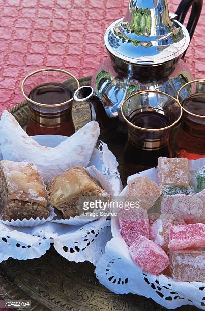 baklava turkish delight kaab el ghzal and mint tea - doilie stock photos and pictures