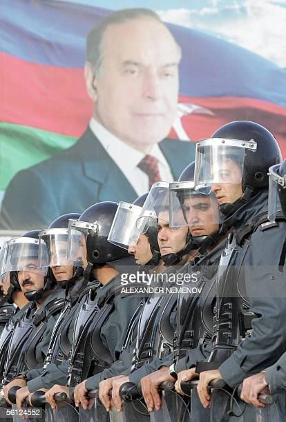 Azeri riot policemen stand guard during the opposition parties rally in Baku 09 November 2005 under the portrait of former Azeri president Heidar...