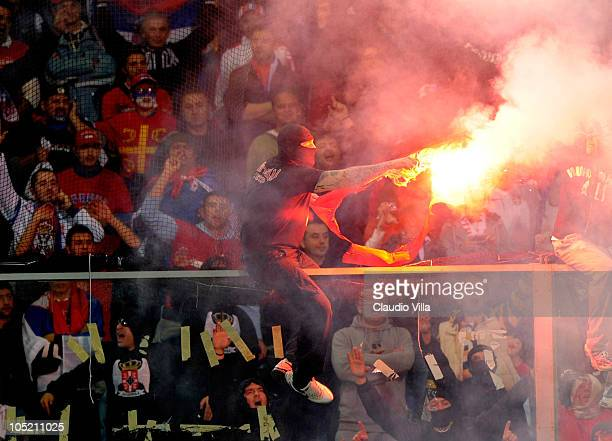 Balaclava clad Serbian fan Ivan Bogdanov gestures towards riot police during the UEFA EURO 2012 Group C qualifier between Italy and Serbia at Luigi...