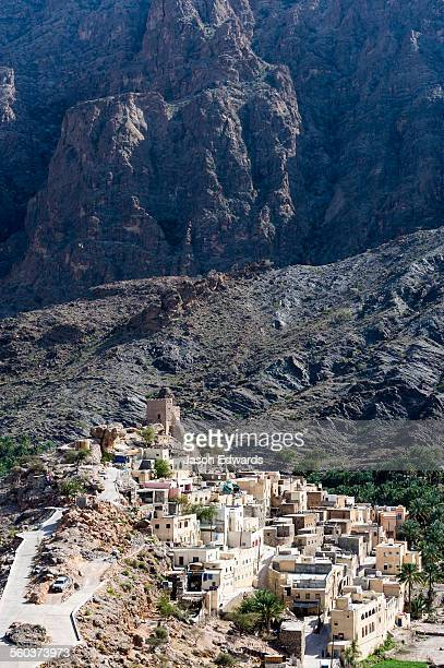 A mountain village stacked on terraced streets in a desert mountain valley.
