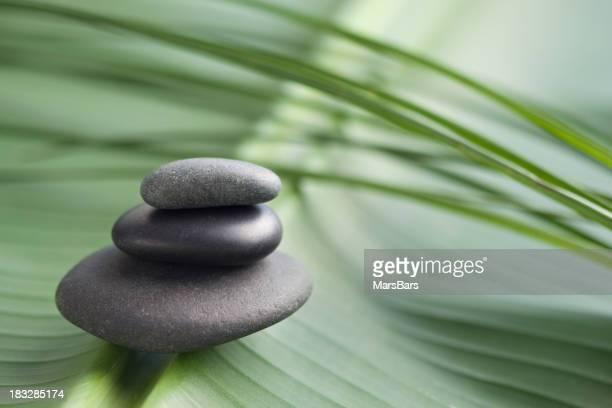 Balanced massage stones on leaf