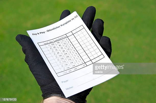 balanced scorecard - holding golf card in hand with gloves