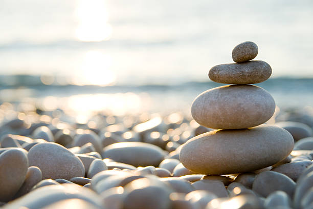 balanced stones on a pebble beach during sunset. - 平衡 個照片及圖片檔