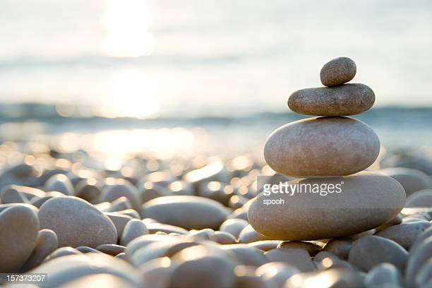 balanced stones on a pebble beach during sunset. - kalmte stockfoto's en -beelden