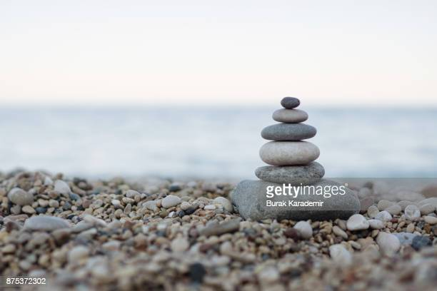 balanced stones on a pebble beach - kalmte stockfoto's en -beelden