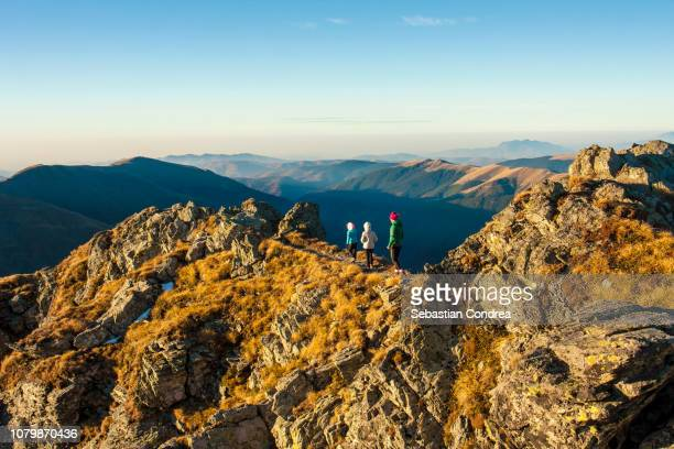 Balancing girls on the ridge of the Vantarea of Buteanu Peak on sunrise, Fagaras mountains, Romania