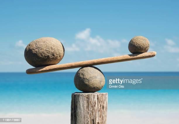 balancing stones, one side heavier - scales balance stockfoto's en -beelden