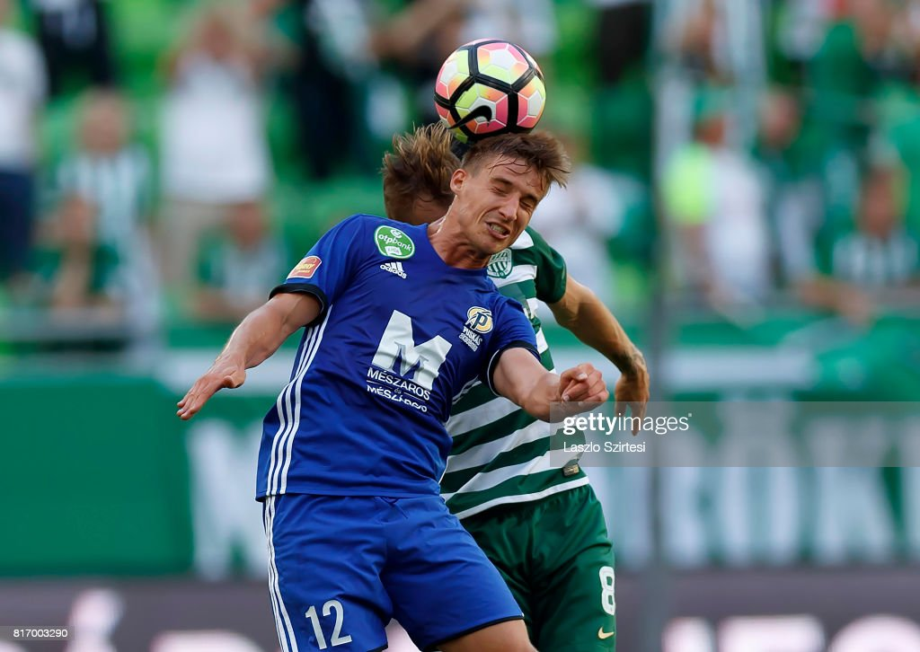 Balazs Balogh #12 of Puskas Akademia FC wins the ball in the air from Gergo Lovrencsics #8 of Ferencvarosi TC during the Hungarian OTP Bank Liga match between Ferencvarosi TC and Puskas Akademia FC at Groupama Arena on July 16, 2017 in Budapest, Hungary.