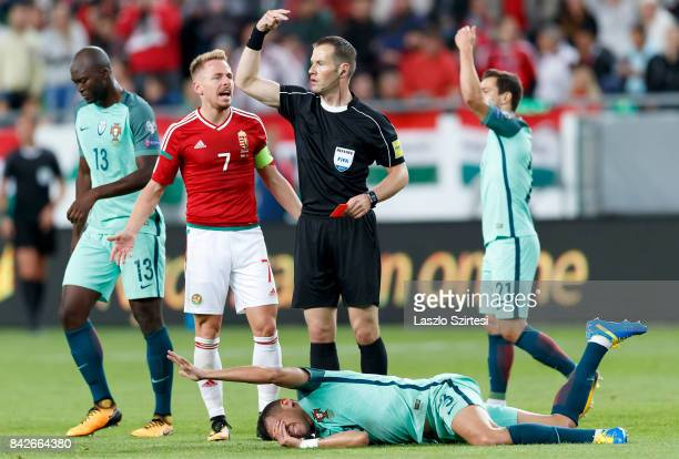 Balazs Dzsudzsak of Hungary argues with referee Danny Makkelie about the sendoff of Tamas Priskin behind Pepe of Portugal during the FIFA 2018 World...