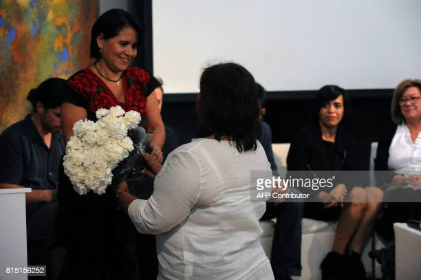 Balbina Flores from Reporters Without Borders presents a bunch of flowers to Griselda Triana de Valdez widow of Mexican slain journalist Javier...
