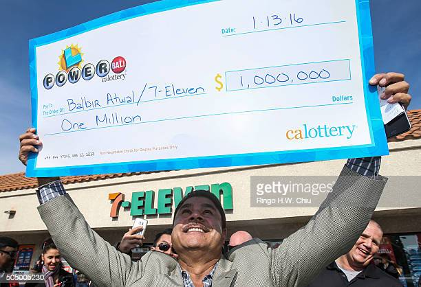 Balbir Atwal owner of the California 7Eleven that sold one of the 3 Powerball winning tickets holds up a $1 million check after received from the...