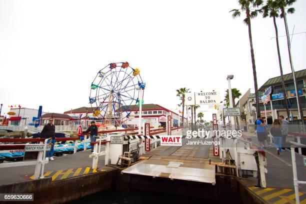 balboa island ferry approaching balboa fun zone, ca - newport beach california stock photos and pictures