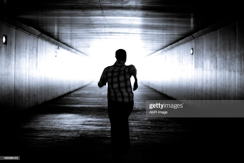 Balck and white image of man's silhouette running : Stock Photo