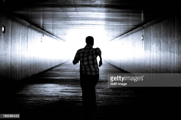 balck and white image of man's silhouette running - fear stock pictures, royalty-free photos & images