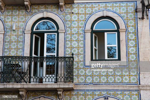 balcony and window with mullion of arches in a facade with tiles