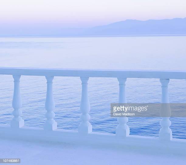 Balcony railing and sea and mountains.