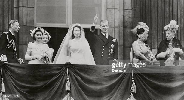 Acknowledging the cheers of thousands of subjects gathered below newlymarried Princess Elizabeth and Prince Philip wave from a balcony at Buckingham...