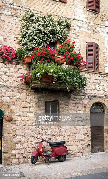 balcony with potted plants and old scooter, assisi umbria italy - vespa brand name stock pictures, royalty-free photos & images
