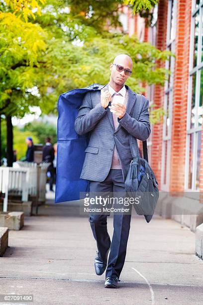 Bald African American man walking home in suit full length