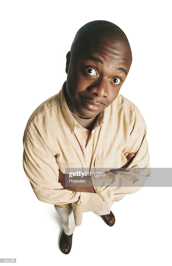 bald african-american man wearing brown sandals and white pants and a cream shirt over a brown shirt crosses his arms as he looks up toward the camera : Foto de stock
