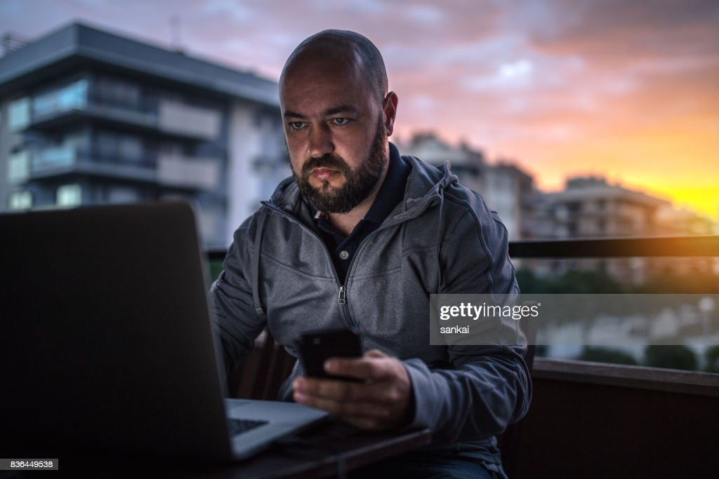 Bald and bearded men uses laptop and smartphone at sunset : Stock Photo