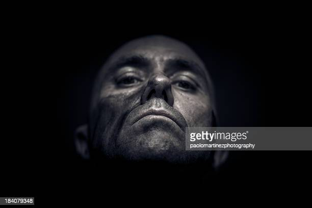 Bald and dirty man's face in the dark
