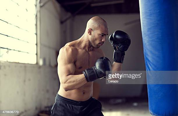 Bald black athletic man boxing in an abandoned warehouse