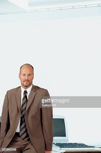 Bald Businessman Alongside His Computer