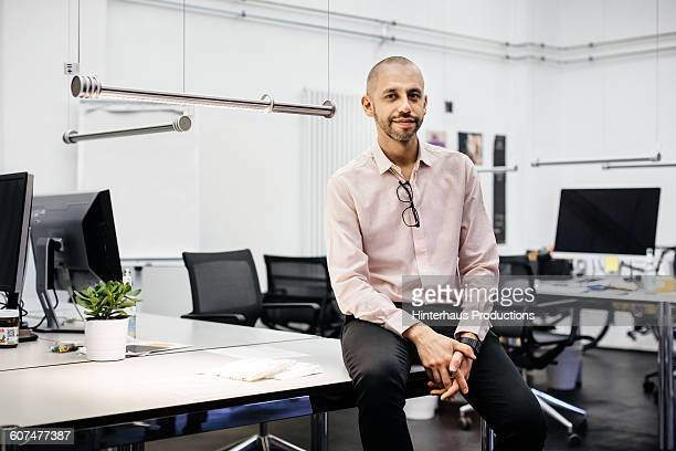 Bald businessman sitting on a desk