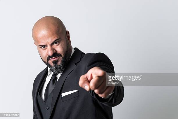 bald businessman with black beard pointing at camera