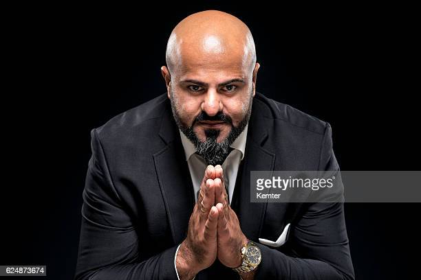 bald businessman with black beard praying - prayer pose greeting bildbanksfoton och bilder
