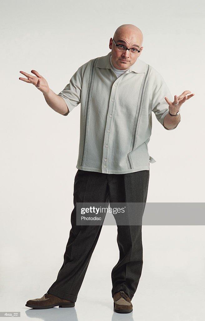 bald caucasian adult male glasses wears slacks cream shirt shrug shoulders expressive look to camera : Foto de stock
