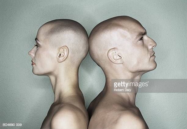 Bald couple standing back-to-back, close-up