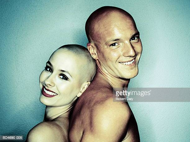 Bald couple standing back-to-back, smiling, portrait