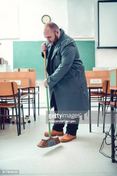 Bald Janitor Cleaning in Engineers Classroom