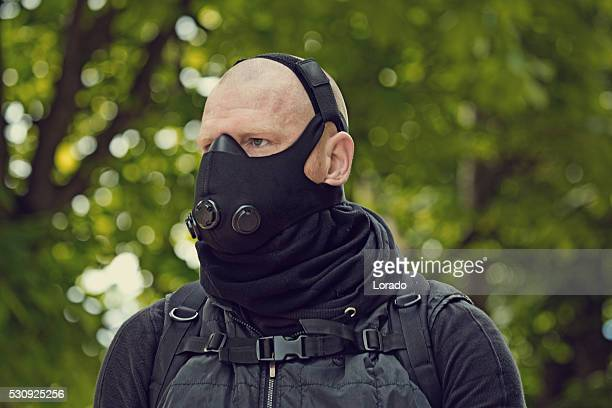 Bald male posing in black in park wearing breathing apparatus