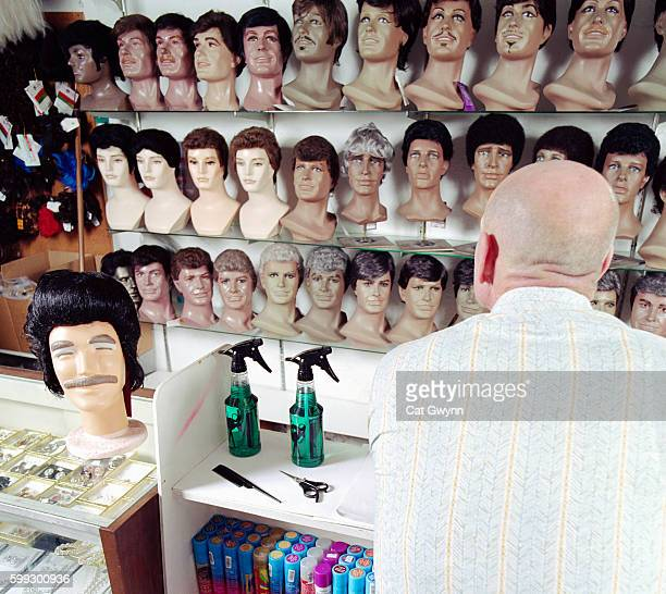 bald man at wig shop counter - wig stock pictures, royalty-free photos & images