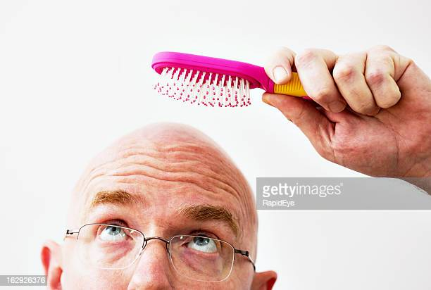 Bald man attempts to brush his non-existent hair