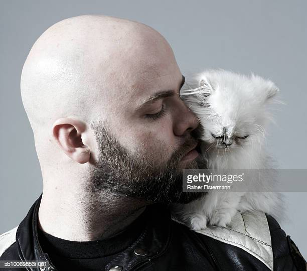 Bald man carrying Persian kitten on shoulder, studio shot