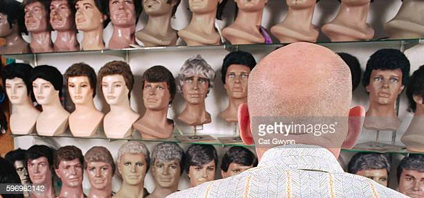 bald man choosing wig from store - wig stock pictures, royalty-free photos & images
