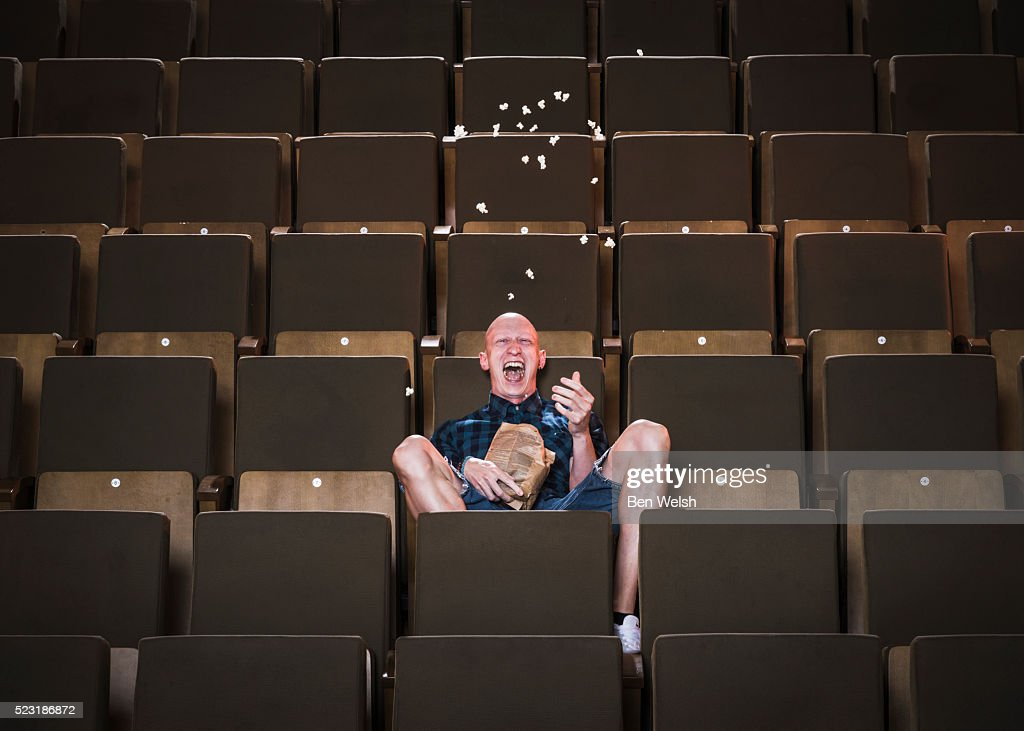Bald man going crazy at the movies. : Stock Photo